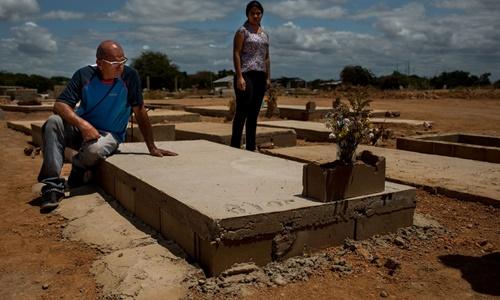 Cha và dì Brito bên ngôi mộ của anh. Ảnh: Bloomberg.