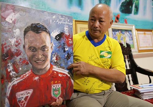 Ông Nguyễn Trọng Hường bên tấm tranh mà một cổ động viên vẽ để tặng Trọng Hoàng. Ảnh: Nguyễn Hải.