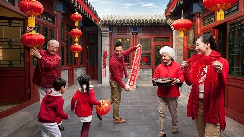 Một gia đình ba thế hệ ở Trung Quốc trang trí nhà cửa chuẩn bị đón Tết. Ảnh: CGTN.