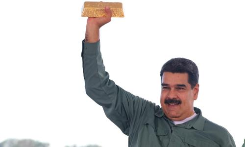 Tổng thống Venezuela Nicolas Maduro giơ một thỏi vàng trong chuyến thăm thành phốPuerto Ordaz hồi tháng 12/2017. Ảnh: Reuters.