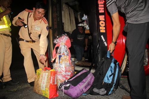 Cảnh sát đưa hành lý và quà Tết của hành kháchra khỏi xe. Ảnh: Nguyễn Khoa.