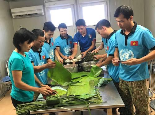 Các thành viên bệnh viện dã chiến cùng nhau gói bánh để tổ chức tiệc tất niên, mời bạn bè quốc tế và tặng cho người dân bản địa.