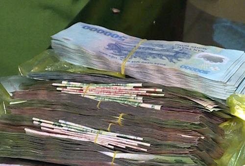 Trong túi xách bà Quắn và ông Lợi nhặt được có hơn 120 triệu đồng. Ảnh: Vĩnh Nam