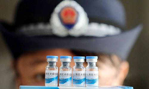 Cán bộ hành pháp Trung Quốc đưa một lô vắcxin đi kiểm tra. Ảnh: EPA.