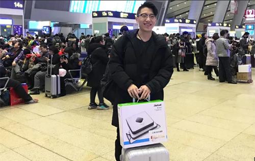 Ông bố trẻ mua quà công nghệ tặng con khi về Tết ở nhà ga Thâm Quyến. Ảnh: SCMP