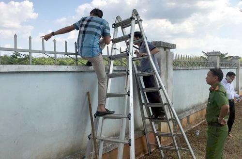 Cảnh sát khám nghiệm bức tường nơi vị trí 2 tên cướp đột nhập và tẩu thoát. Ảnh: Thái Hà