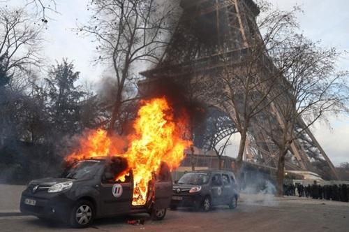 Xe quân sự chống khủng bố bị người biểu tình đốt gần Tháp Eiffel hôm 9/2. Ảnh: AFP.