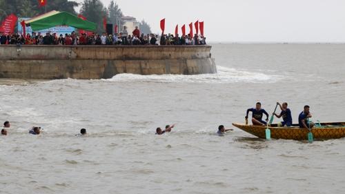 Sóng lớn, gió to buộc các vận động viên bơi thuyền rồng của các đội tham gia hội thi bơi thuyền rồng truyền thống trên biển Đồ Sơn phải bơi ra thuyền neo ở xa bờ. Ảnh: Giang Chinh