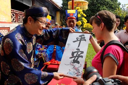 Du khách tham quan Hoàng cung Huế thích thú khi được nhận chữ. Ảnh: Võ Thạnh