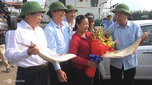 Ông Nguyễn Đức Chính (bên phải) tặng hoa cho gia đình ngư dân trúng mẻ cá 150 tấn. Ảnh: Hoàng Táo