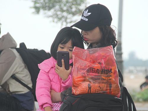 Người lớn và trẻ em đều mệt mỏi khi ngồi bên đường chờ xe nhiều tiếng. Ảnh: Đức Hùng
