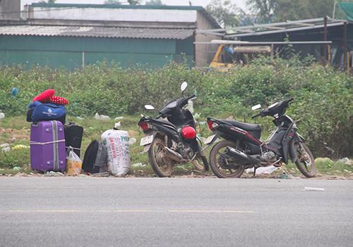 Nhiều người để sẵn hành lý bên quốc lộvào quán nước nghỉ ngơi, khi có xe thì chạy ra vẫy. Ảnh: Đức Hùng