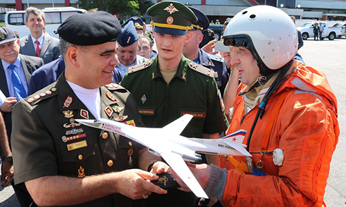 Bộ trưởng Quốc phòng Venezuela Vladimir Padrino Lopez (bên trái) nhận mô hình oanh tạc cơ Tu-160 từ tay phi công Nga (bên phải, áo cam). Ảnh: FANB.