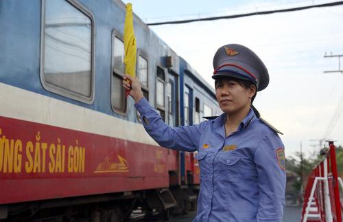 Chị Minh ra hiệu cờ thông tàu tại chốt gác chắn Hãng Dầu, TP Biên Hòa. Ảnh:Phước Tuấn.