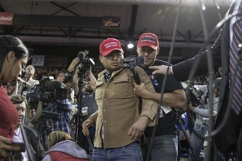 Người đàn ông (mũ đỏ, đeo kính) bị khống chế sau khi tấn công phóng viên BBC. Ảnh: Bloomberg.