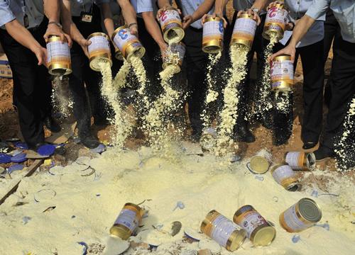 Giới chức đổ bỏ sữa bột trong vụ bê bối sữa nhiễm melamine năm 2008. Ảnh: CNN.