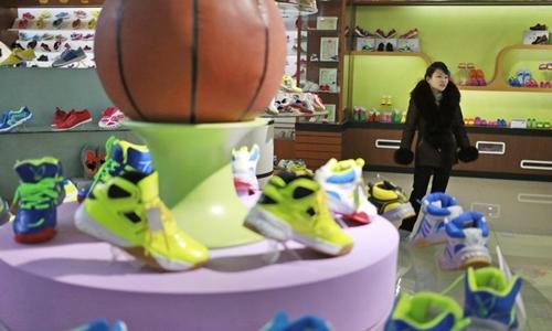 Kim Kyong Hui, hướng dẫn viên của nhà máy giày Ryuwon trong phòng trưng bày của nhà máy hôm 1/2. Ảnh: AP.