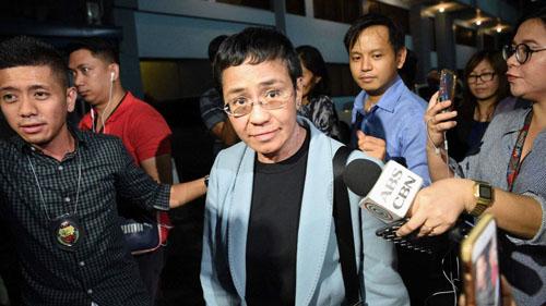 Ressa (giữa) bị áp giải vào trụ sở Cục Điều tra quốc gia sau khi bị bắt hôm 13/2. Ảnh: AFP.