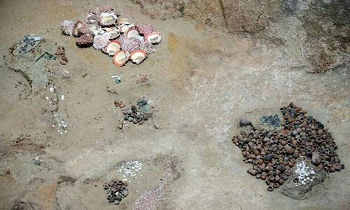 Vỏ sò Spondylus và các bình gốm bên trong ngôi mộ. Ảnh: Phys.