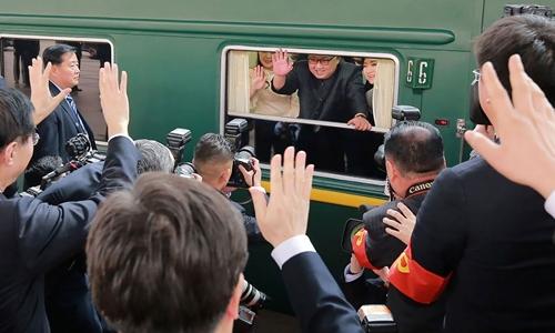 Kim Jong-un (đeo kính) đứng trên tàu vẫy tay khi chuẩn bị rời khỏi Bắc Kinh tháng 3/2018. Ảnh: KCNA.