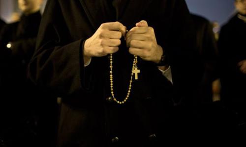 Một linh mục cầm chuỗi hạt công giáo cầu nguyện. Ảnh: BBC.
