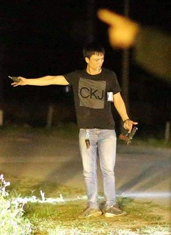 Nghi phạm Trung cầm súng và lựu đạn trước mặt cảnh sát.