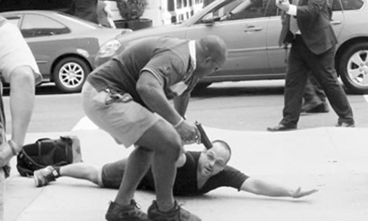 Phóng viên ảnh nằm rạp xuống đất sau khi bị mật vụ mặc thường phục rút súng khống chế năm 2011. Ảnh:NYPost.