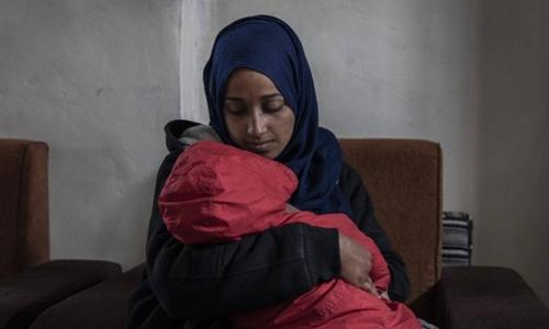 Hoda Muthana, sinh ra tại Mỹ, gia nhập IS 4 năm trước, bế con trai trong trại tập trung ở Al-Hawl, Syria hôm 17/2. Ảnh: NYTimes.