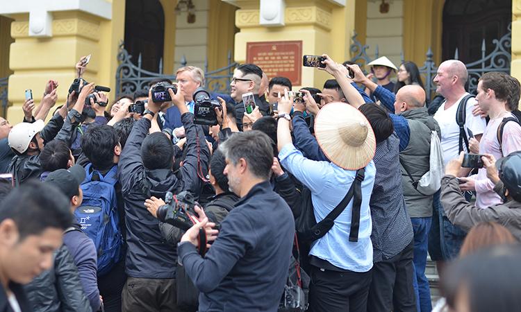 Phóng viên và nhiều người dân hiếu kỳ vây quanh hai người để chụp ảnh. Ảnh: Vũ Anh.