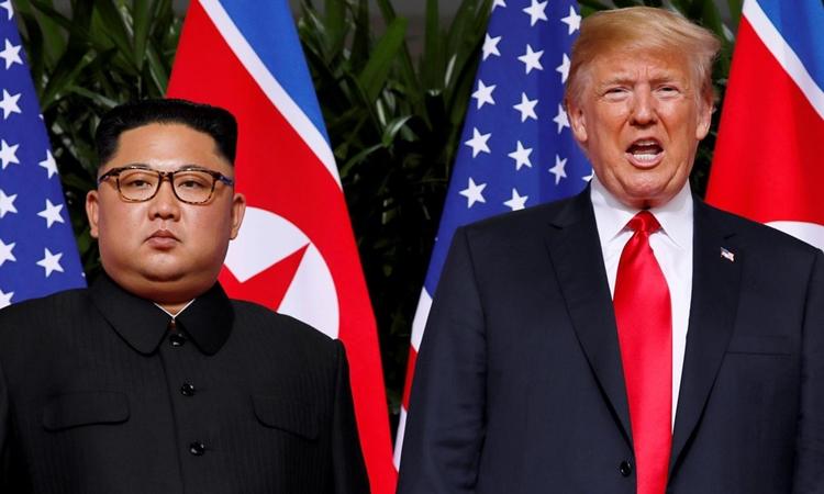 Tổng thống Mỹ Donald Trump (phải) và lãnh đạo Triều Tiên Kim Jong-un tại hội nghị thượng đỉnh đầu tiên ở Singapore hồi tháng 6 năm ngoái. Ảnh: Reuters.