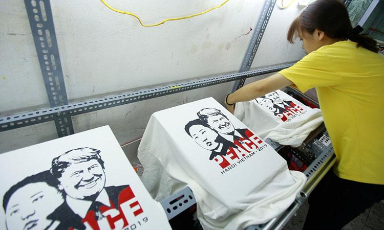 Một người phụ nữ gỡ những chiếc áo phông in hình Tổng thống MỹDonald Trump và lãnh đạo Triều Tiên Kim Jong-un tại một cửa hàng ở Hà Nội vào ngày 21/2. Ảnh: AP.