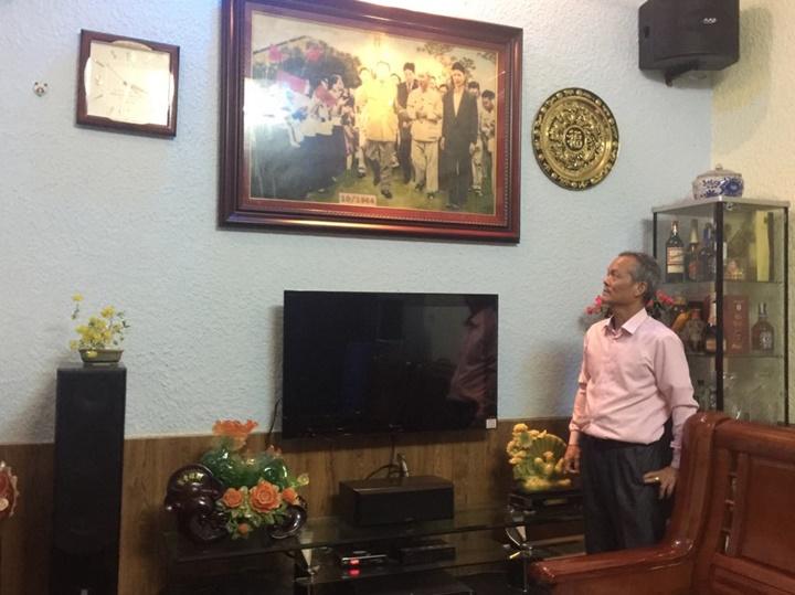 Ông Nguyễn Văn Hải ngước nhìn bức tranh đá phóng tác từ  bức ảnh bố, ông Nguyễn Văn Vượng (comple tối màu) tiếp đón Kim Nhật  Thành và Chu tịch Hồ Chí Minh được treo ở phòng khách.