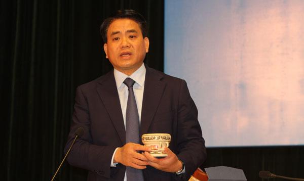 Chủ tịch Hà Nội Nguyễn Đức Chung giới thiệu mô hình trống đồng làm từ gốm Chu Đậu để tặng các phóng viên quốc tế và trong nước đến đưa tin hội nghị thượng đỉnh Mỹ - Triều. Ảnh:Võ Thành.