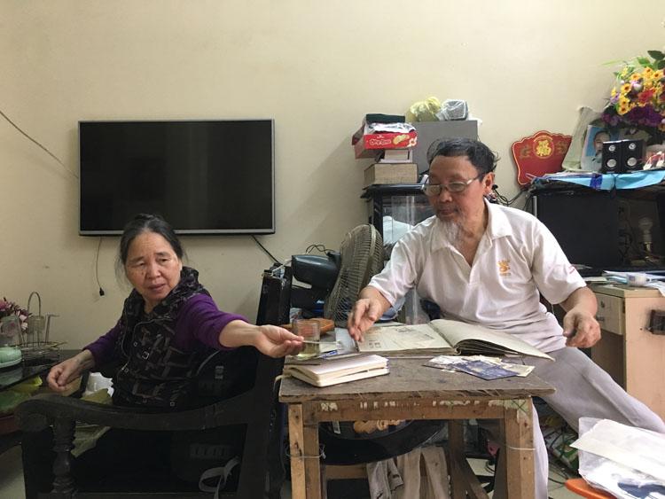 Ông Lê Ngọc Túc (phải) và vợ tìm lại những bức ảnh chụp ở Triều Tiên tại nhà riêng ở thành phố Thanh Hóa. Ảnh: Hạnh Phạm.