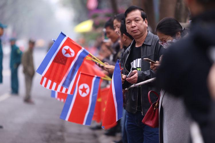 Người dân cầm cờ Việt Nam, Mỹ, Triều Tiên đứng chờ đoàn xe Chủ tịch Kim Jong-un đi qua. Ảnh: Phạm Dự.