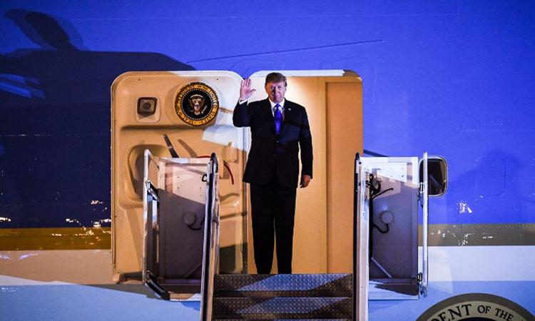 Tổng thống Trump vẫy chào trên chuyên cơ Không lực Một khi tới sân bay Nội Bài tối 26/2. Ảnh: AFP.