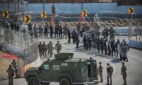 Binh sĩ và cảnh sát Mỹ dựng hàng rào tạm tại khu vực biên giới với Mexico. Ảnh: AFP.