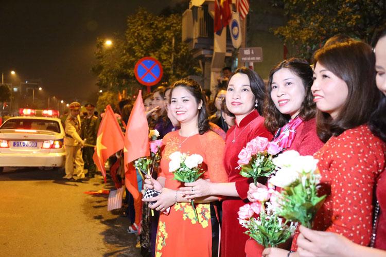 Người dân Việt Nam cầm cờ, hoa đón chào Tổng thống Mỹ Donald Trump tới Hà Nội tối 26/2. Ảnh: Phạm Dự.