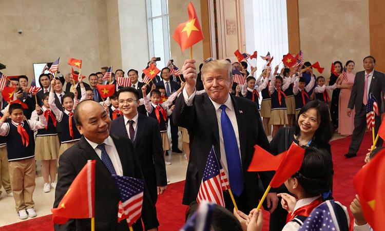 Tổng thống Trump giơ cao lá cờ Việt Nam trong sự chào đón của cán bộ và các em thiếu nhi. Ảnh: Reuters.