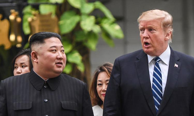 Chủ tịch Triều Tiên Kim Jong-un và Tổng thống Mỹ Donald Trump đi dạo trong khuôn viên khách sạn Metropole tại Hà Nội, phía sau là hai nữ phiên dịch. Ảnh: CNN.