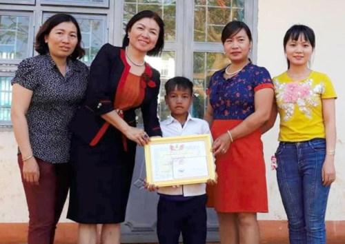 Gơng (giữa) nhận giấy khen và phần thưởng của nhà trường. Ảnh: Trần Hóa.