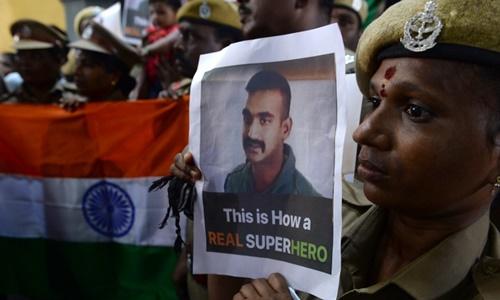 Một người giơ ảnh phi công Abhinandan Varthaman để chào đón anh này về nước ngày 2/3. Ảnh: AFP.