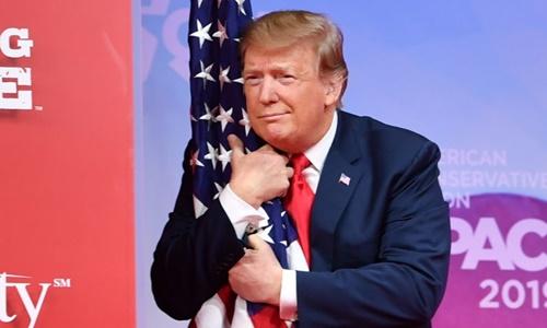 Ông Trump ôm cờ tại Hội nghị Hành động Chính trị Bảo thủ ngày 2/3. Ảnh: AFP.