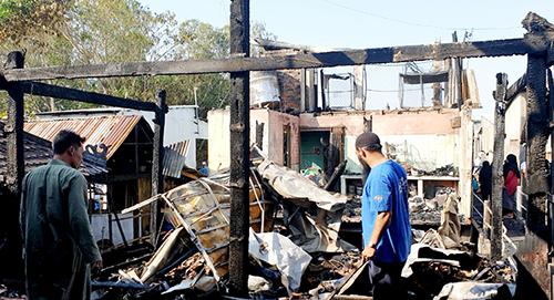 Người dân tìm kiếm các vật dụng còn sót lại trong ngôi nhà cháy. Ảnh: Nguyễn Huynh