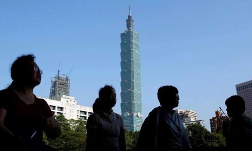 Du khách đi qua tòa nhà Đài Bắc 101 của Đài Loan tháng 7/2016. Ảnh: Reuters.