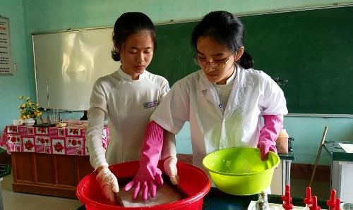 Hai nữ sinh thực hiện công đoạn sản xuất giấy theo phương pháp thủ công trong phòng thí nghiệm. Ảnh: Võ Thạnh