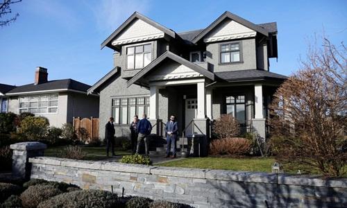 Nhân viên an ninh túc trực bên ngoài căn nhà của Mạnh Vạn Chu ở Vancouver hồi tháng một. Ảnh: Reuters.