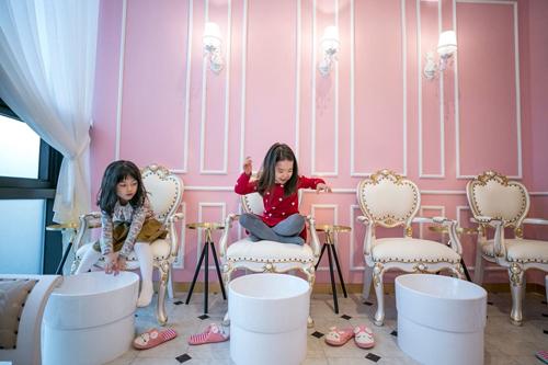 Hai bé gái chơi đùa tại quán cafe PriPara ở ngoại ô Seoul, được miêu tả là nơi tràn ngập niềm vui và không nguy hiểm để trẻ em học về vẻ đẹp và biết cách ăn vận. Ảnh: Washington Post.