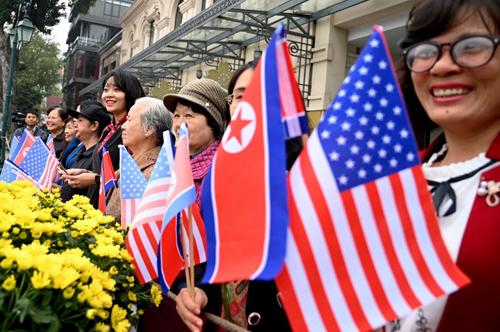 Người dân Việt Nam cầm cờ Mỹ và Triều Tiên vẫy chào đoàn xe chở lãnh đạo hai nước tới hội nghị thượng đỉnhhôm 28/2. Ảnh: AFP.