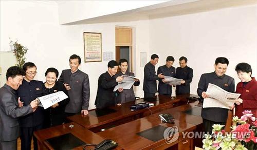 Công nhân viên Triều Tiên đọc báo về chuyến thăm của Kim Jong-un đăng trên báo Rodong Sinmun hôm 6/3. Ảnh: Yonhap.